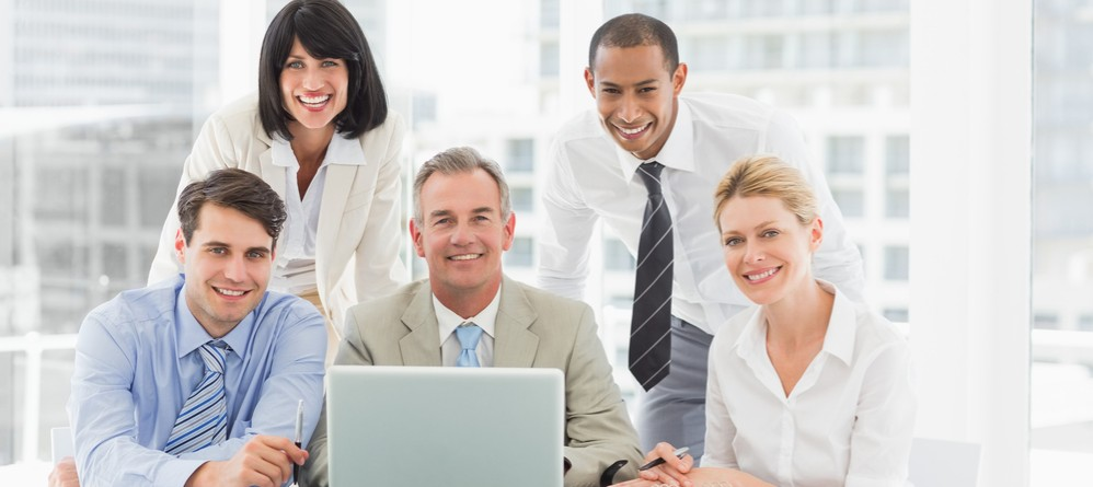 Happy business people gathered around laptop looking at camera in the office