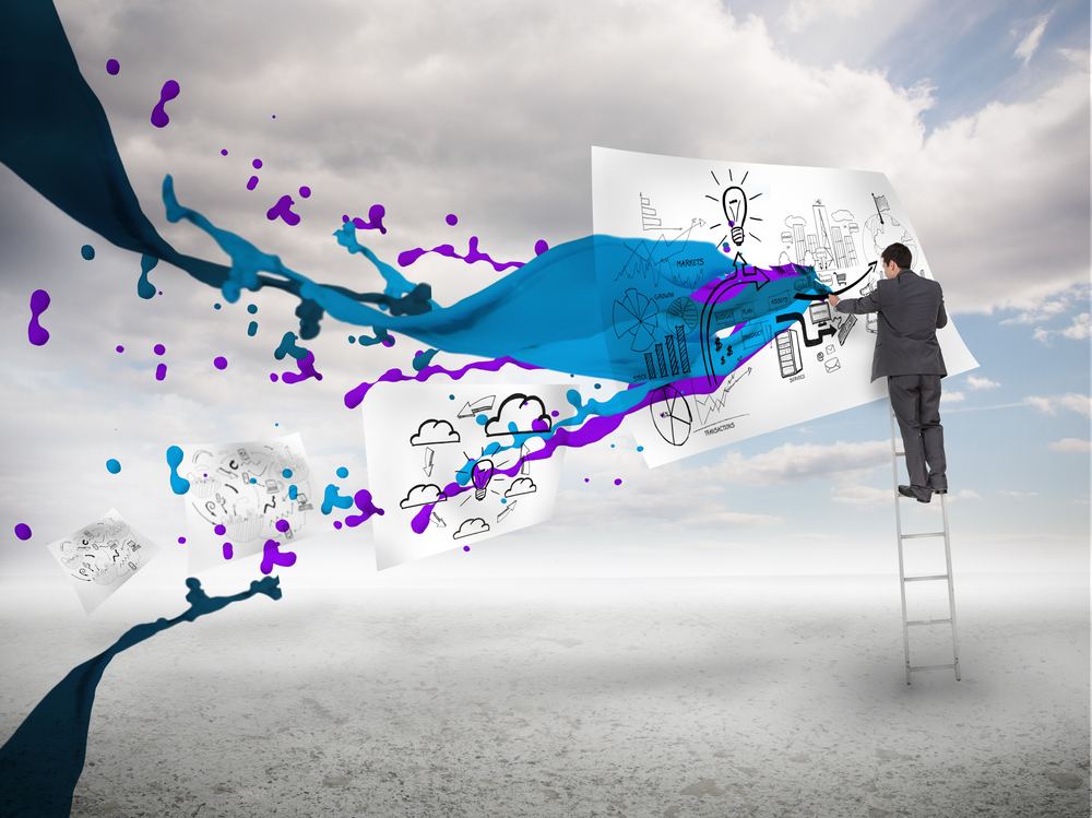 Businessman drawing on a paper next to paints splash with blue sky on the background