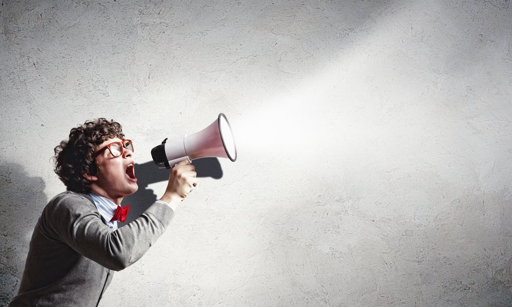 Portrait of young man shouting loudly using megaphone