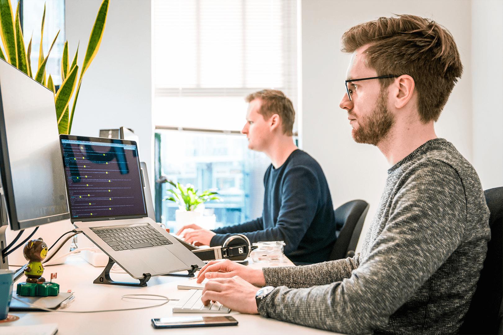 2 men using laptops in office